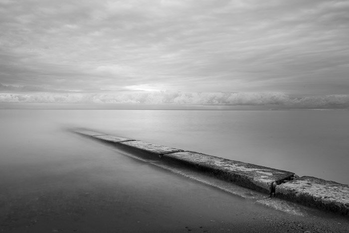Long exposure photograph of barrier stretching into water at sunrise monochrome