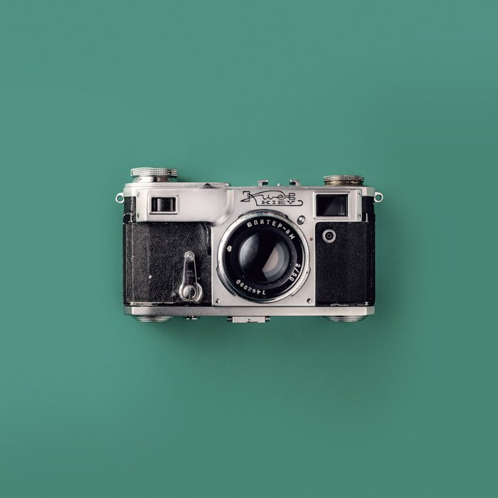 Grey and Black Rangefinder Camera On Green Background