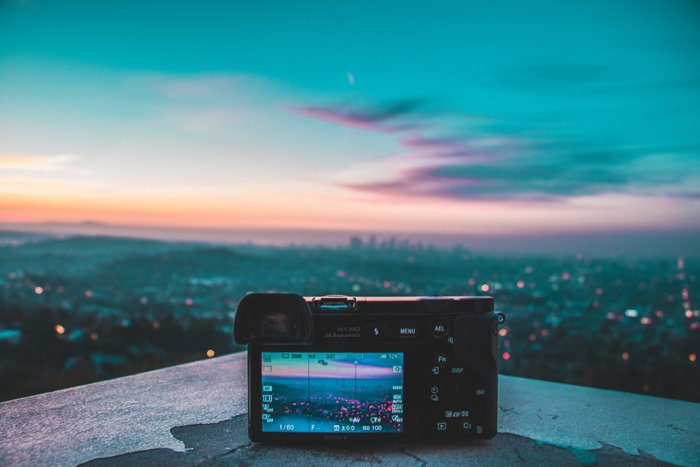 an image of a mirrorless camera set on a ledge overlooking a city skyline at dusk