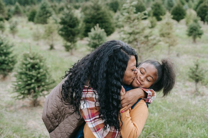 mother kissing daughter in grassy area