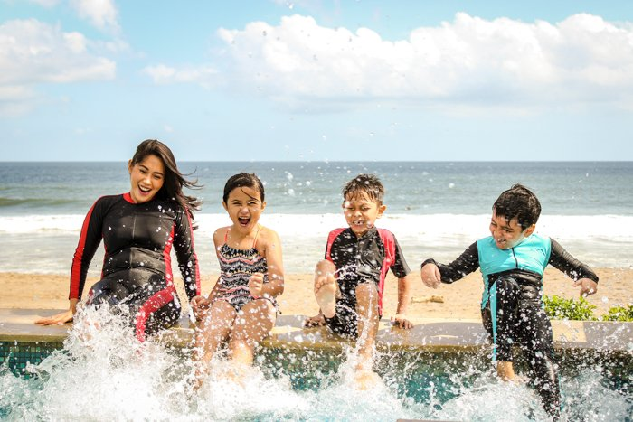 Family photos of 4 children playing in the ocean