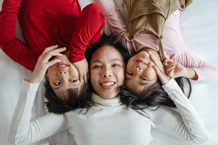 three women photographed on bed from above