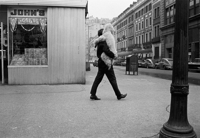 Man carrying toy in black and white photo by Joel Meyerowitz