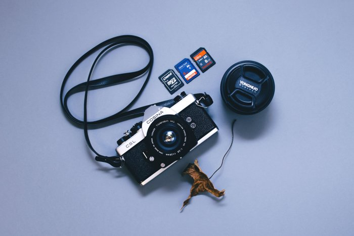 A camera besides numerous memory cards and a lens cap
