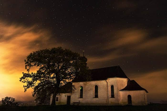 Long exposure night photography of a small church and a tree under the night sky