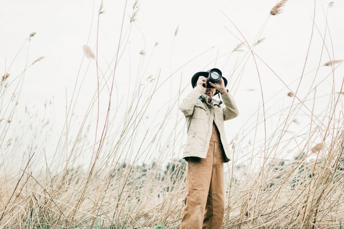 an image of a man in a wheat field holding a camera to his face