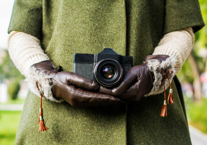 an image of a person holding a camera with a set of brown gloves on
