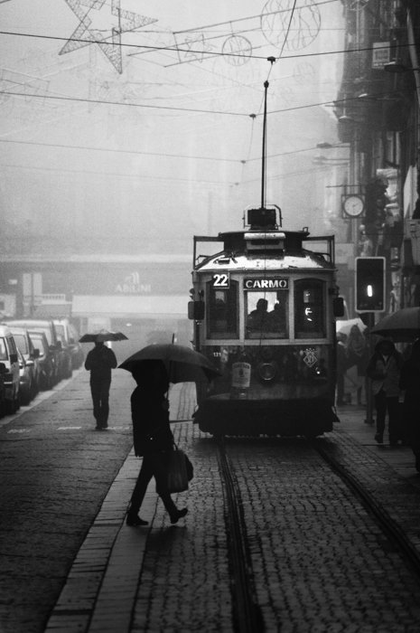 black and white image of a man with umbrella crossing a tram