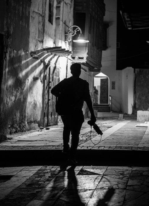 black and white silhouette of a photographer near a street light