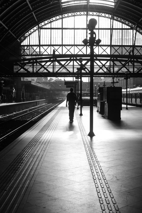 black and white image of a man walking on a platform in a train station