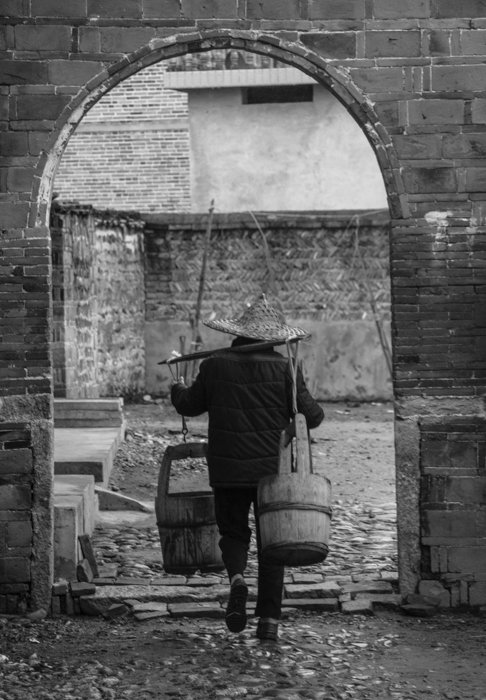black and white image of a man in a cap walking through an arch