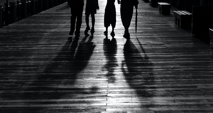 black and white image of four people waist-down and with shadows
