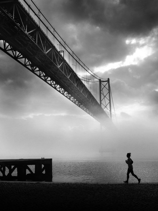 black and white image of a runner with the misty Golden Gate in the background