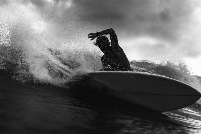black and white image of a man with a surfboard in the waves