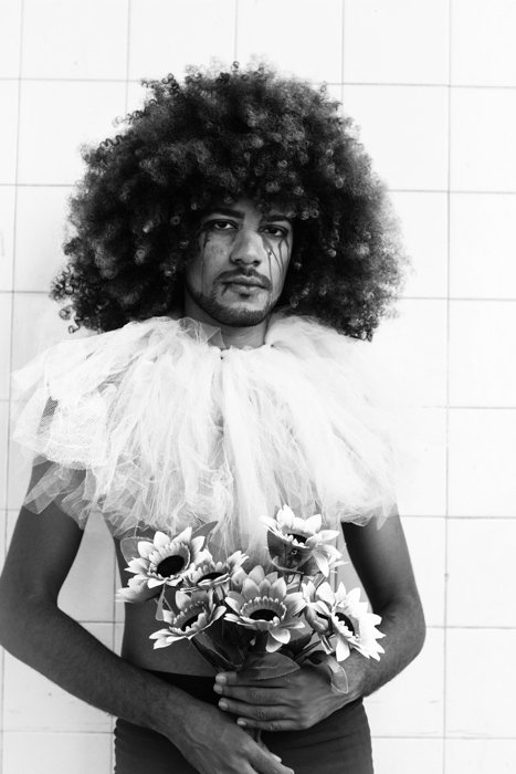 stylistic image of a person with an afro holding fake flowers