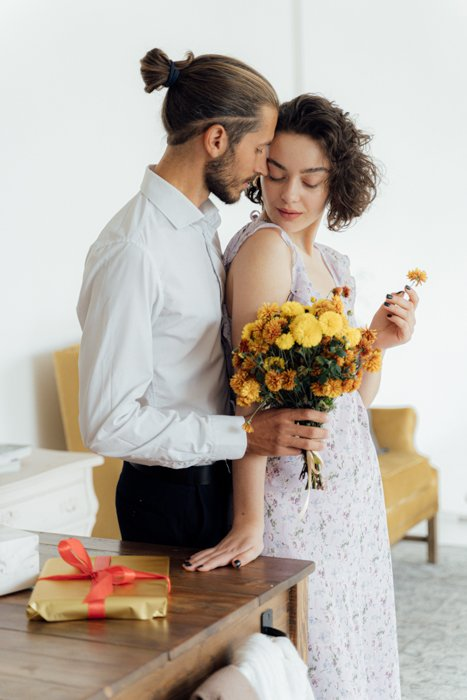 An intimate image of a young couple while the guy handles a flower bucket over the girl from the back.