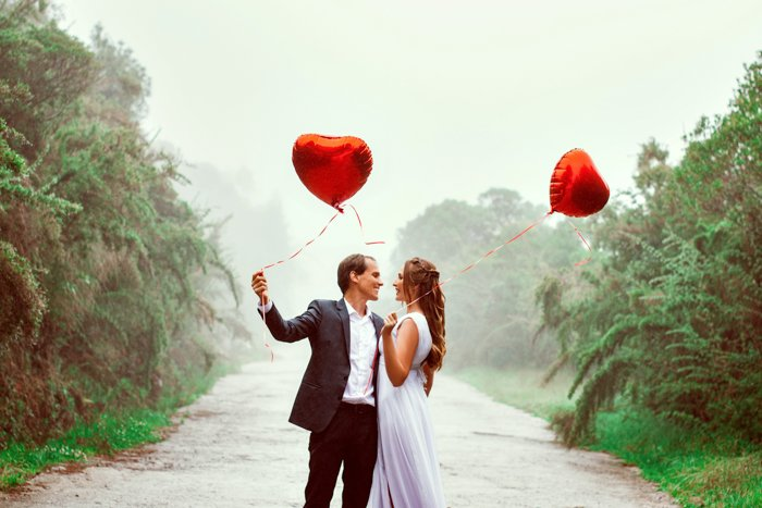 A picture of an elegant couple holding heart shaped balloons.