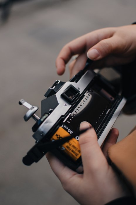 A man loading a roll of 35mm film into his analog camera