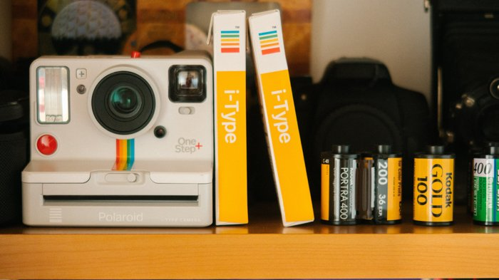 An image of a Polaroid instant camera and instant films besides 35m film rollsm film rolls