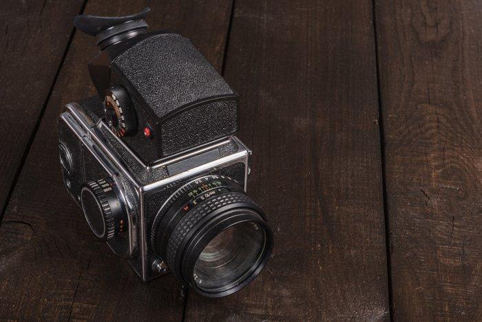 A medium format film camera on a wooden table