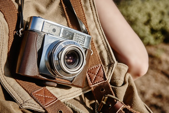 An image of a vintage camera on a leather backpack