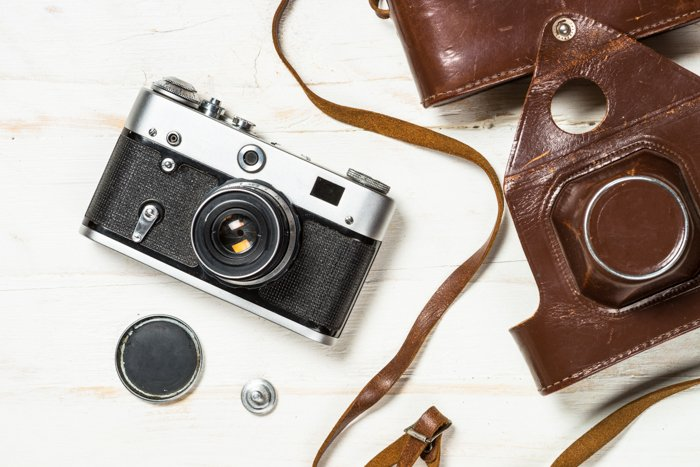 A vintage analog camera in leather casing and its accessories on a table