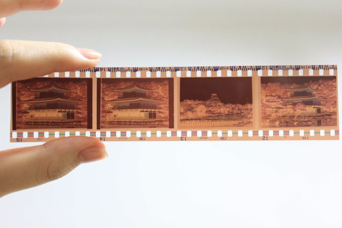 A hand holding a slide of 35mm negative