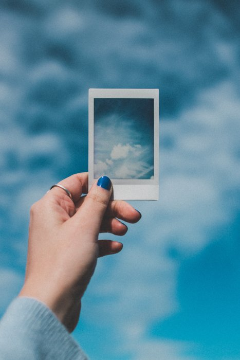 A hand holding a picture from an instant camera