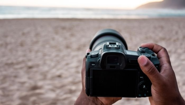 person holding dslr camera on the beach