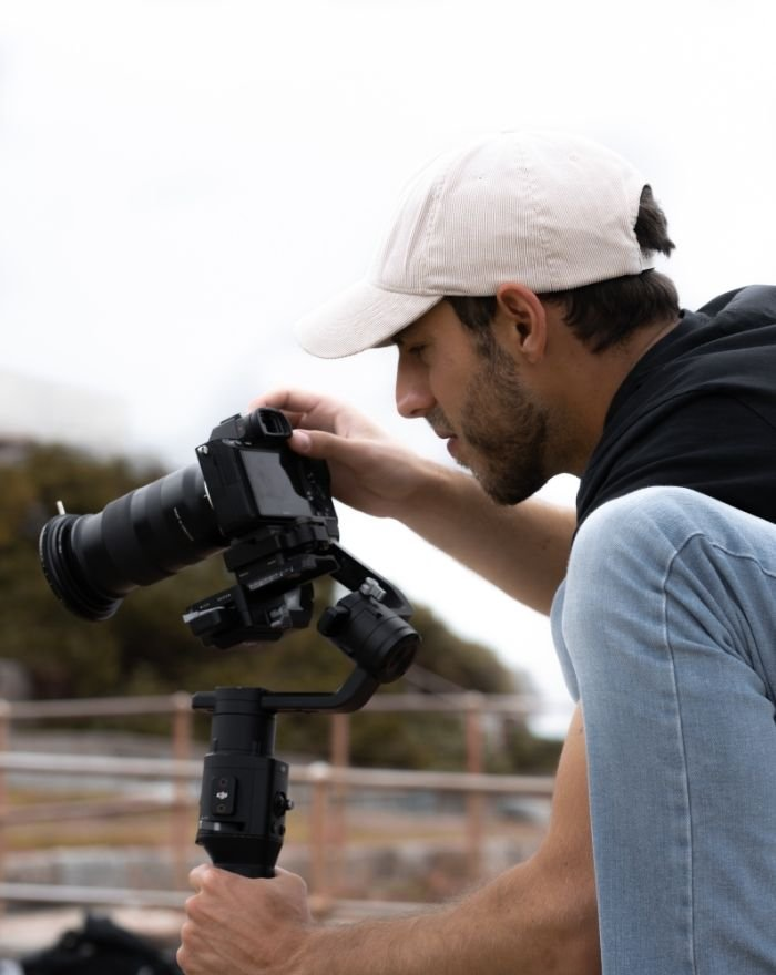 Man in black shirt and jeans looking through a Dslr Cameras viewfinder