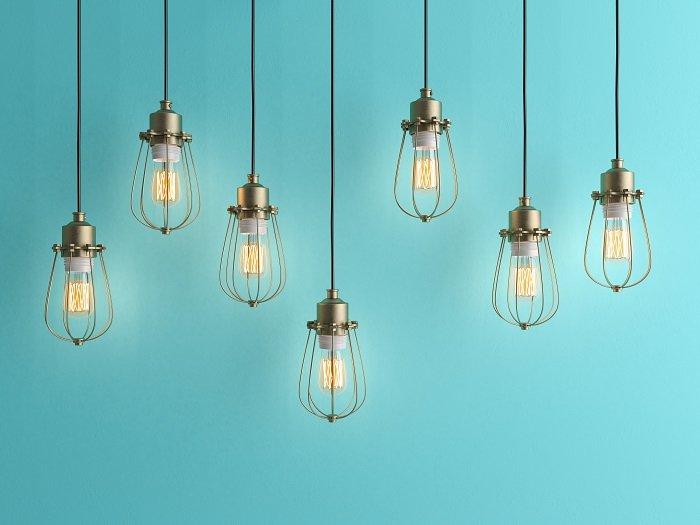Seven vintage lamps hanging against a blue background