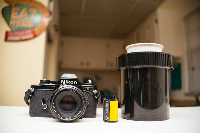 uma imagem de uma câmera de filme Nikon, uma bobina de filme e um tanque de revelador em uma mesa
