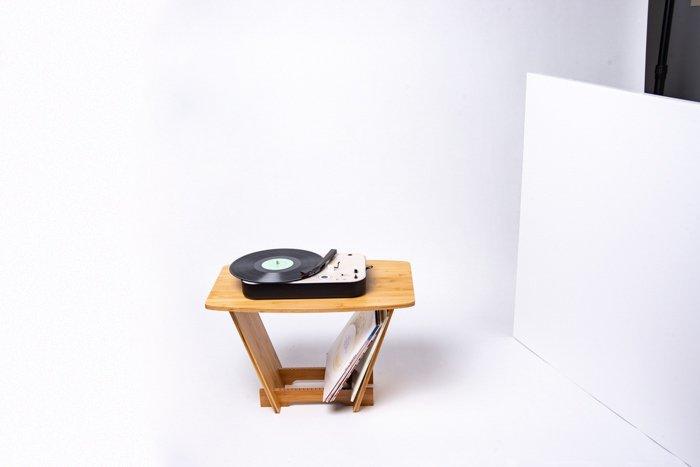 Um toca-discos em cima de uma mesa em um fundo branco.