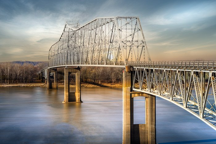 an image of a sky replacement above a bridge crossing a river