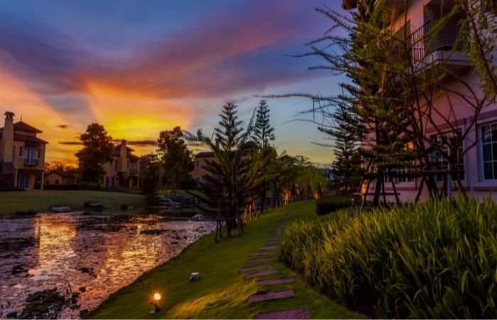 Foto do crepúsculo de um vilarejo com casas luxuosas de estilo europeu perto de um belo jardim ambiental
