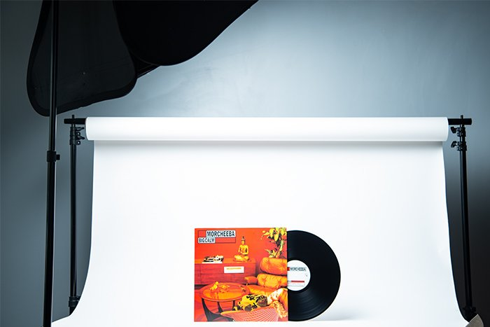 Vinyl record against a white background illuminated from an angle