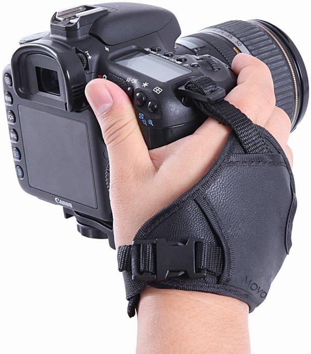 A closeup of a hand, holding a DSLR camera with a wrist strap