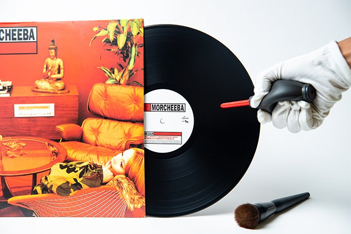 A hand using an air blaster to remove dust on a vinyl record