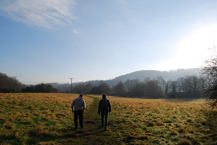 two people walking in a trail through a field