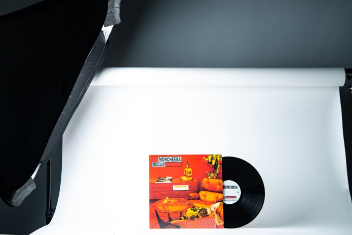 Vinyl record against a white background illuminated from the side