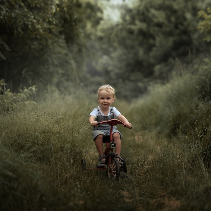 child riding a tricycle through a woodland trail