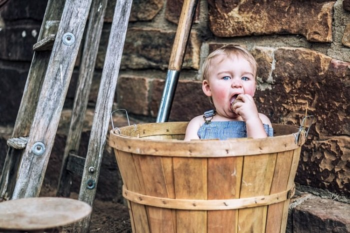 child sitting in a bucket for a creative rustic image