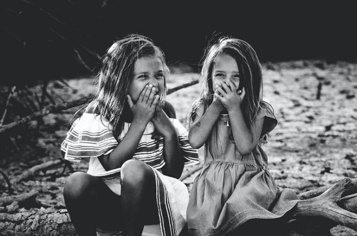 children laughing while covering their mouths