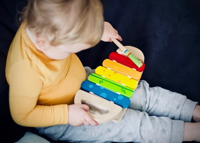 child playing with a xylophone