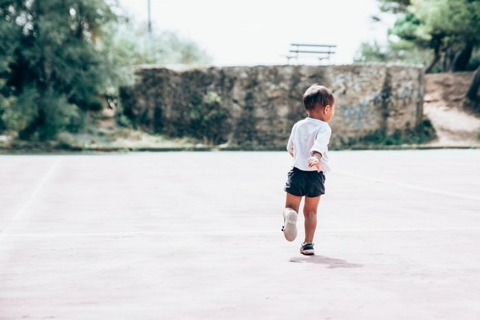 Child running away from the camera in a park