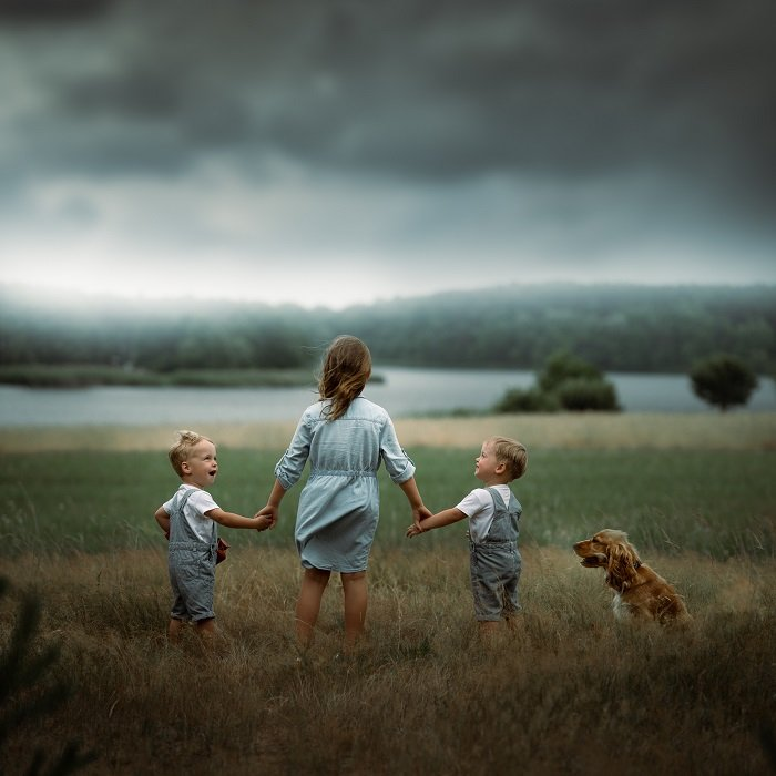three siblings and a dog on a dramatic countryside landscape