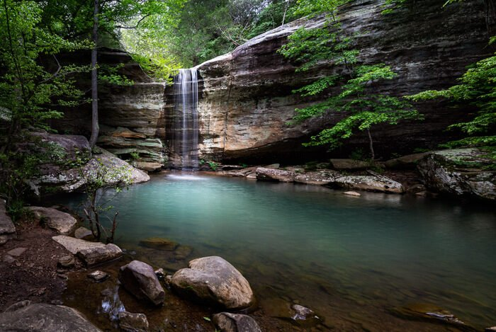 A small hidden waterfall in the wood to show landscape photography settings for blurred water