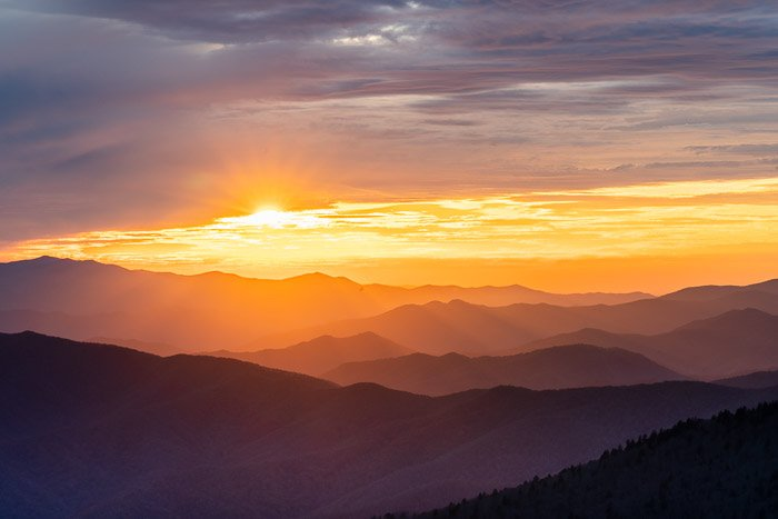 Sunrise image of mountain ranges to show best landscape photography settings for HDR