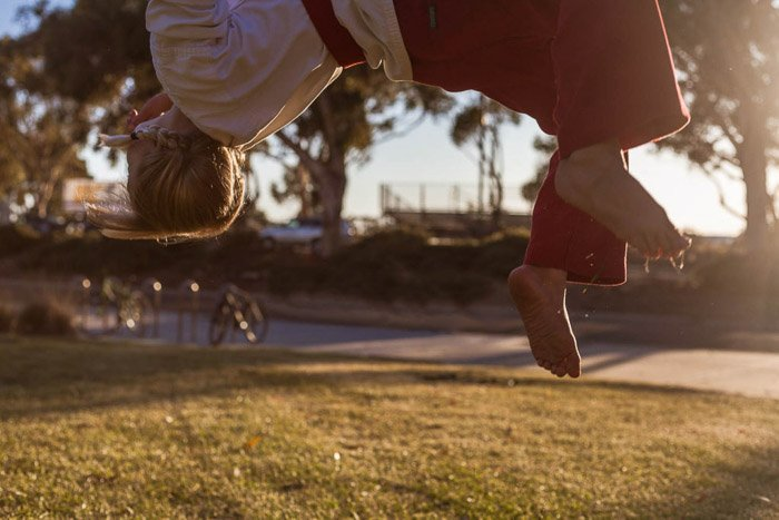 Candid child photo of a girl doing a backflip wearing martial arts clothing