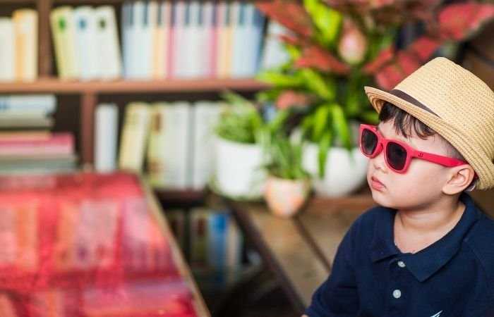 candid child photography of a little boy wearing a summery hat and sunglasses